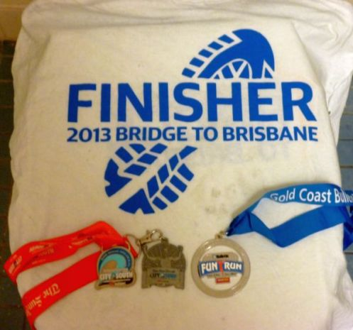 Medals for City2South (LEFT), City2Surf (Middle) and Gold Coast Bulletin Fun Run (Right) draped over the Bridge2Brisbane finishers shirt